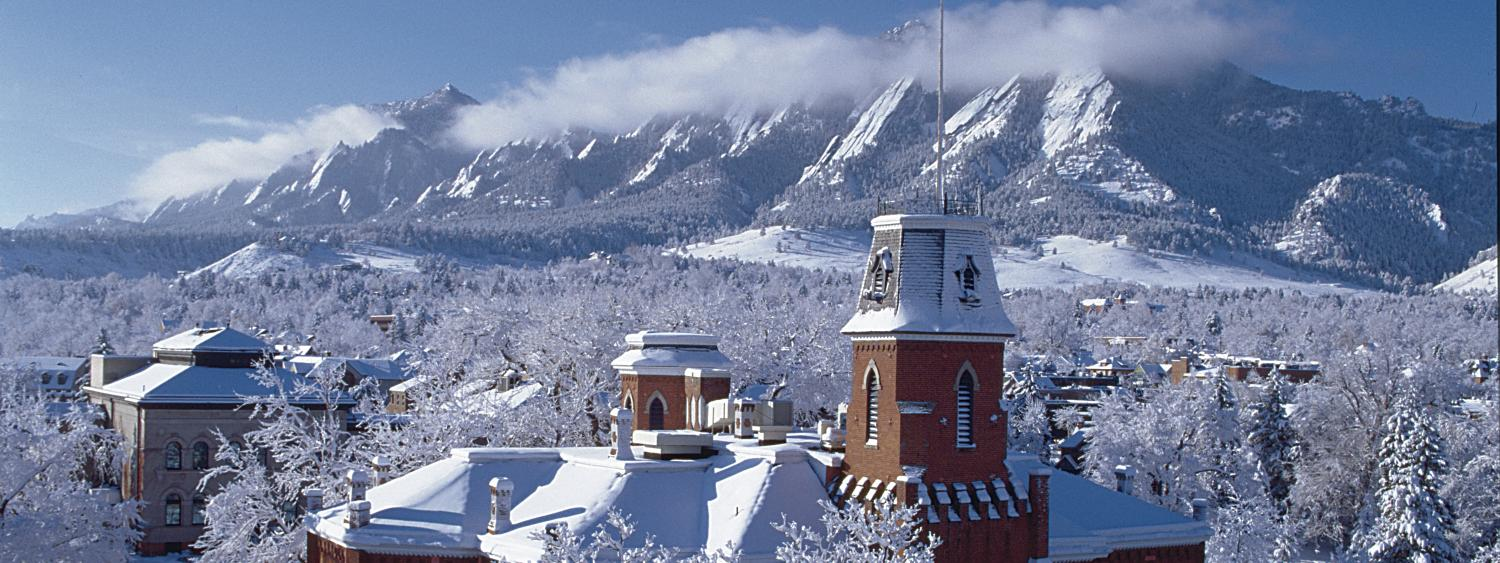 A snow-covered CU Boulder campus is shown with the Flat Irons in the background.