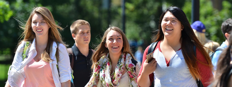 Three girls walking, smiling and talking on campus
