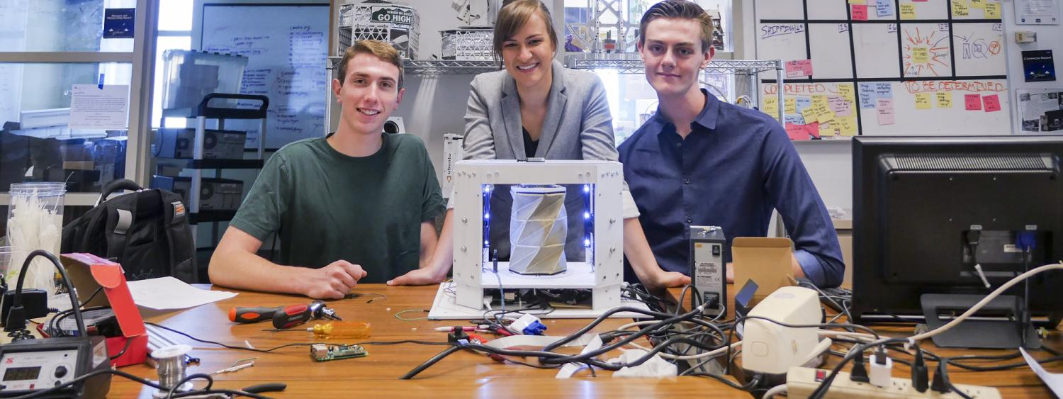 Andrew Pfefer, Anastasia Muszynski and Dawson Beatty pose with their inflatable, collapsable device with origami-type folds
