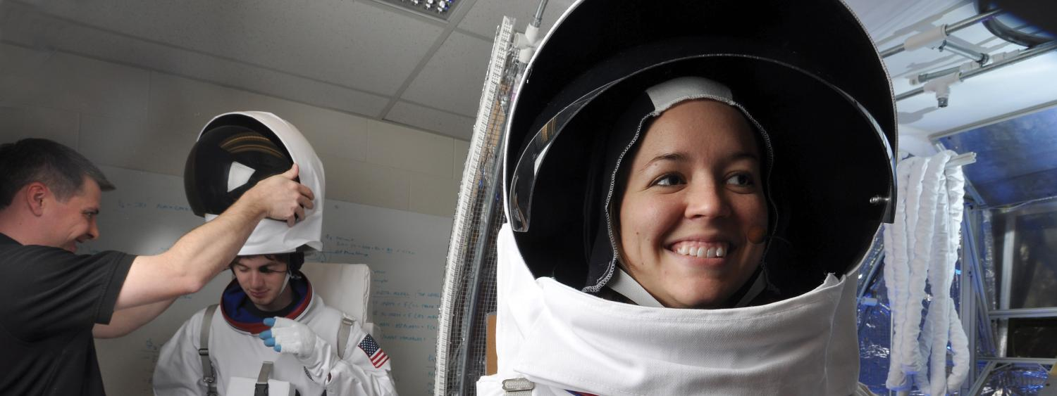 Student smiles while wearing spacesuit