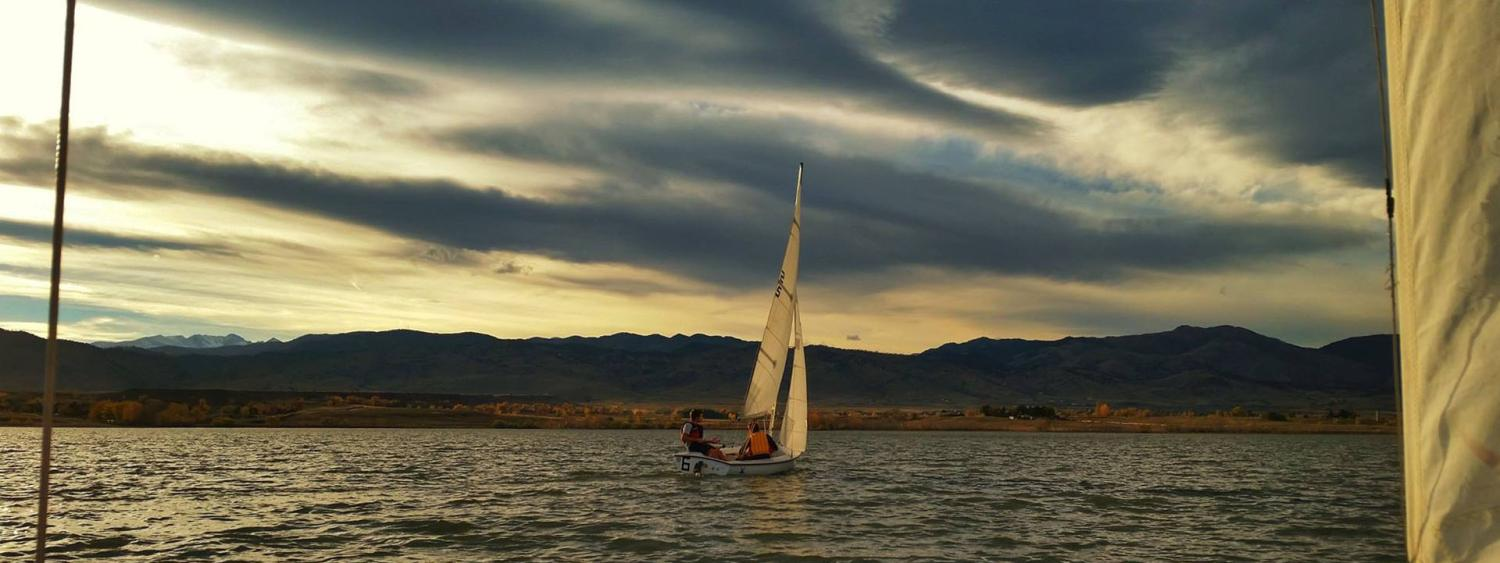CU sailing team sails in water with the mountains in the background.