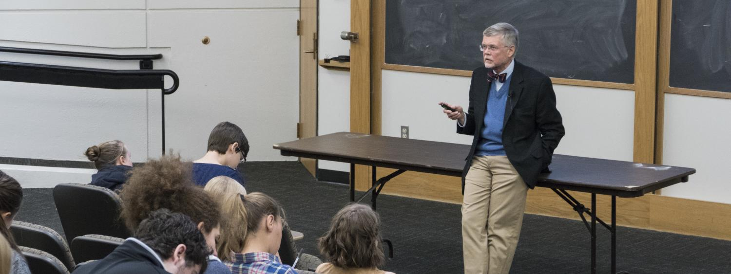 Professor stands in front of a class taking notes in an auditorium