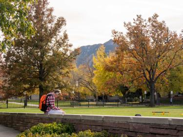 Student outside on CU Boulder campus in the Fall