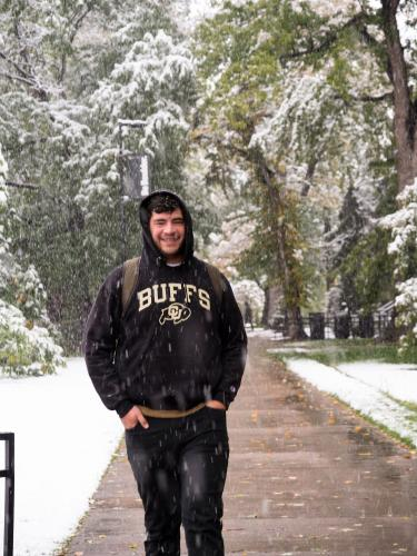 Student walking through falling snow on campus