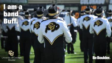 """The back of band members in formation on a field with """"I am a band Buff"""""""