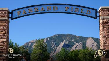 Sign over Farrand Field with Flatirons in the back