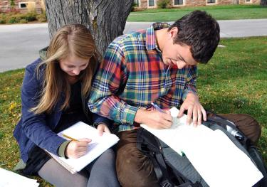 Students writing outdoors
