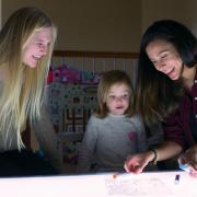 Researcher and children smiling at light table