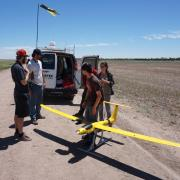 Students inspecting a drone in front of the van