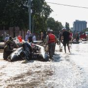 People and rescuers on flooded street in Houston