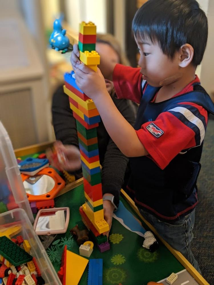 Child building lego tower