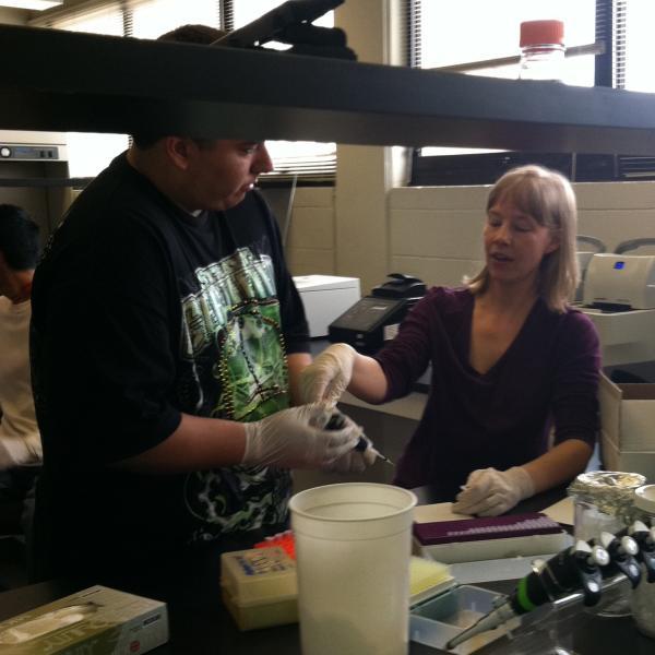 Stacey supervises pipetting practice. Northeast Upward Bound Program, June 21, 2011