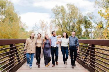 Frances Draper and her family walk across a Boulder bridge. Pictured left to right are Draper's husband Michael Minard; Draper; daughter-in-law Justine Fallon; son Karl Kumli with Draper's grandchild; daughter Anneka Kumli; and soon-to-be-son-in-law Tom Dole.