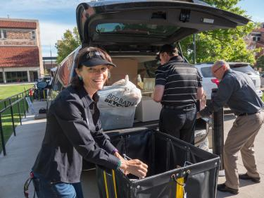 Frances Draper and Provost Russell Moore, in the background on the right, are pictured helping students during fall move-in.