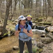 Abby Benson and her son hike through a forest in her home state of Rhode Island.