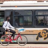 Person riding bike next to Buff Bus