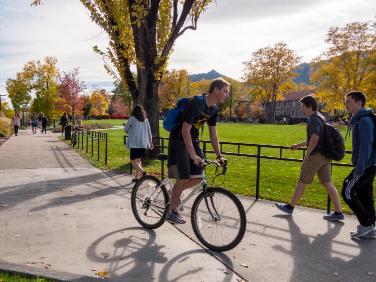 Male student riding his bike on campus