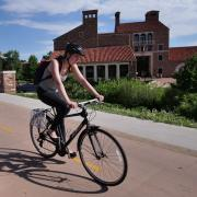 Female student riding bike on campus