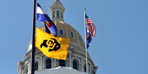 U.S., Colorado state and CU Boulder flags flying at the capitol