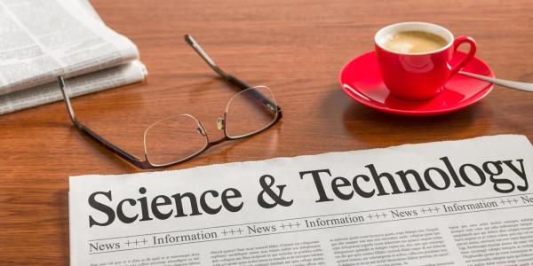 Science and Technology headline on a newspaper, next to eyeglasses and a computer