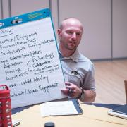 Student Affairs Communications and Marketing Coordinator Jesse Peterson shows his table's communications priorities at the Fall 2018 Campus Communicators Conference