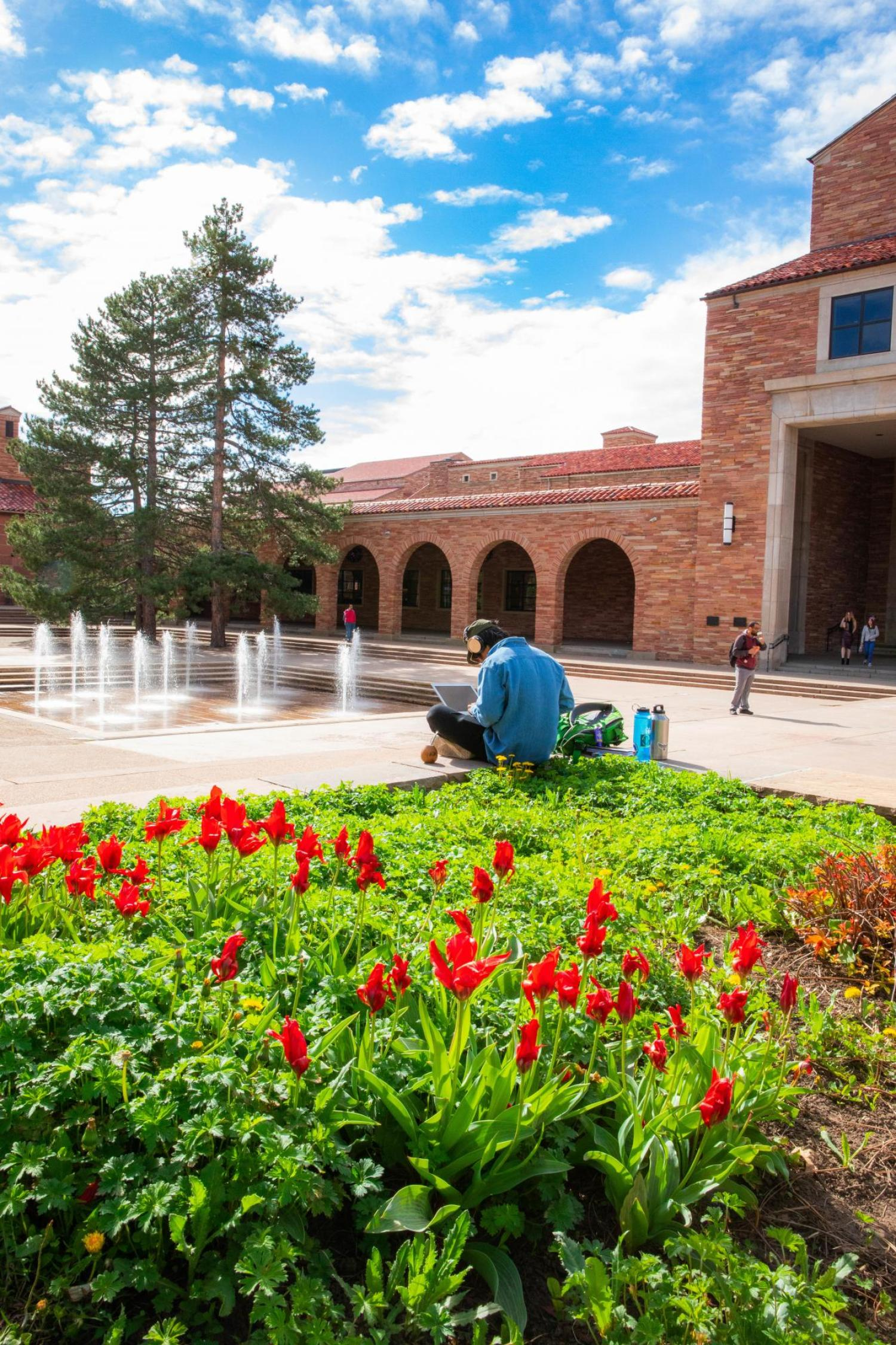 Student outside the UMC fountains in the spring