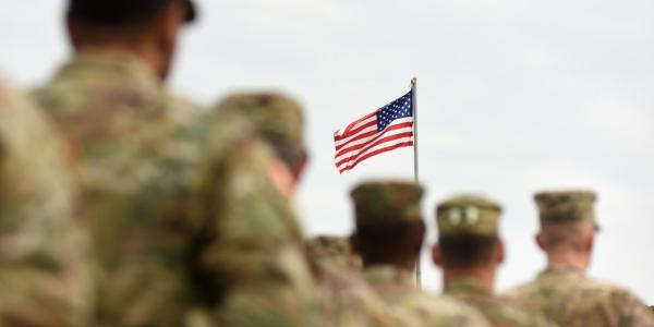 Military personnel with a US flag in the background