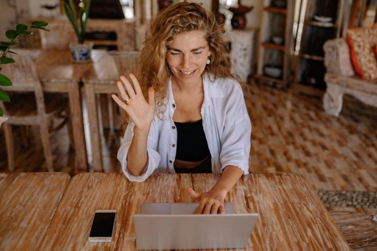 student waving to computer