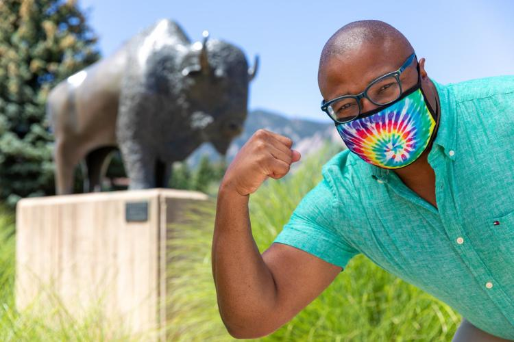 JB Banks posing in front of a buffalo statue