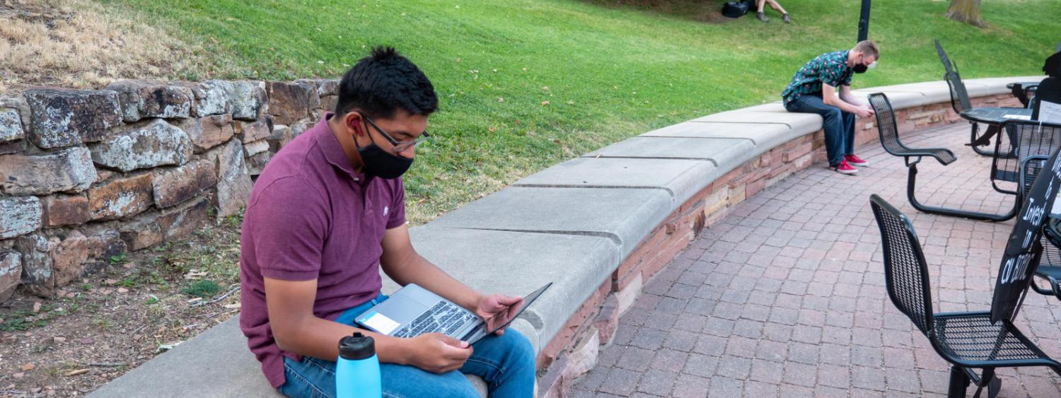 student on lawn with computer
