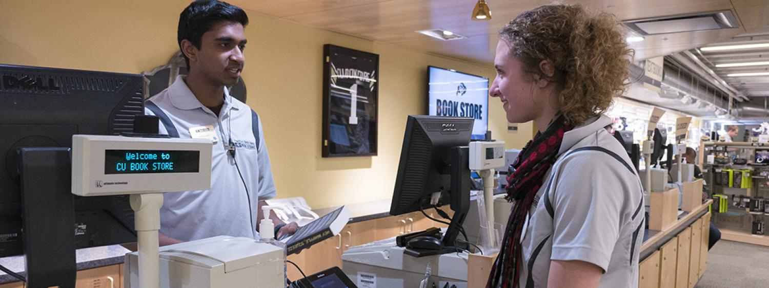 student employee at bookstore assists customer