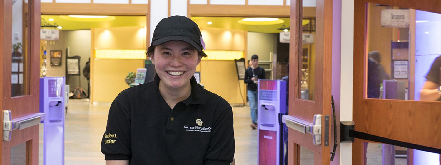Student Employee Smiling in front of Computer