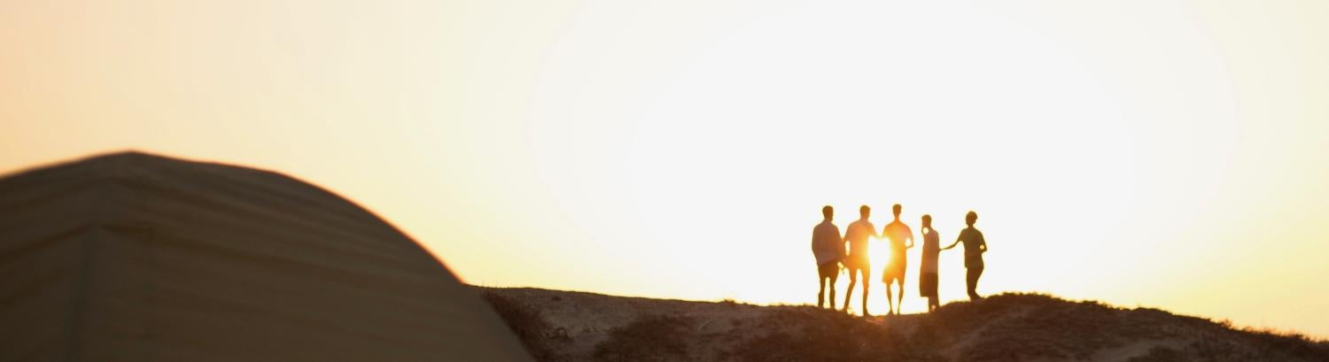 5 guys in silhouette with sun in background