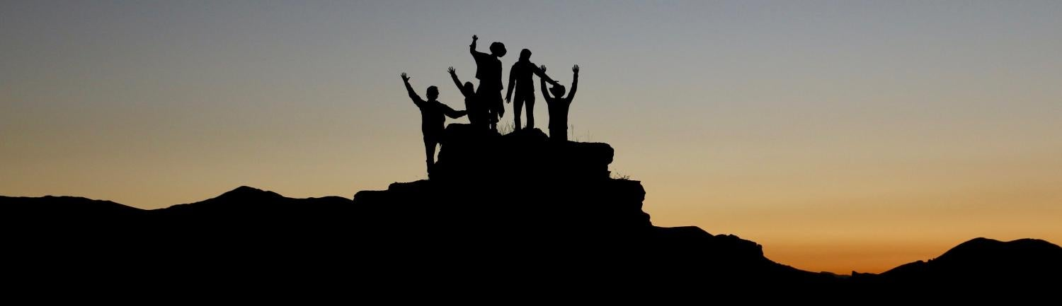 Silhouette of people on rock with background sunset