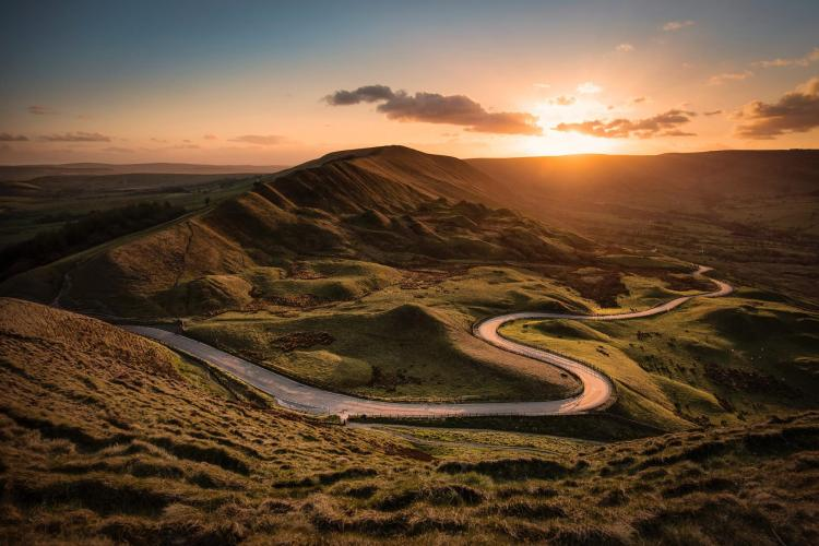 Landscape with twisting mountain road and sunset