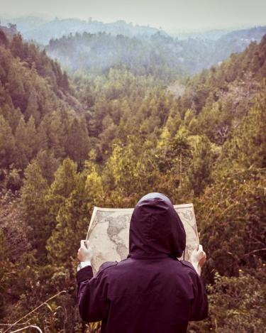 Hooded person looking at map in front of forest valley