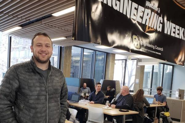 Native Alaskan male stands behind a table promoting STEM Routes at Engineering Week