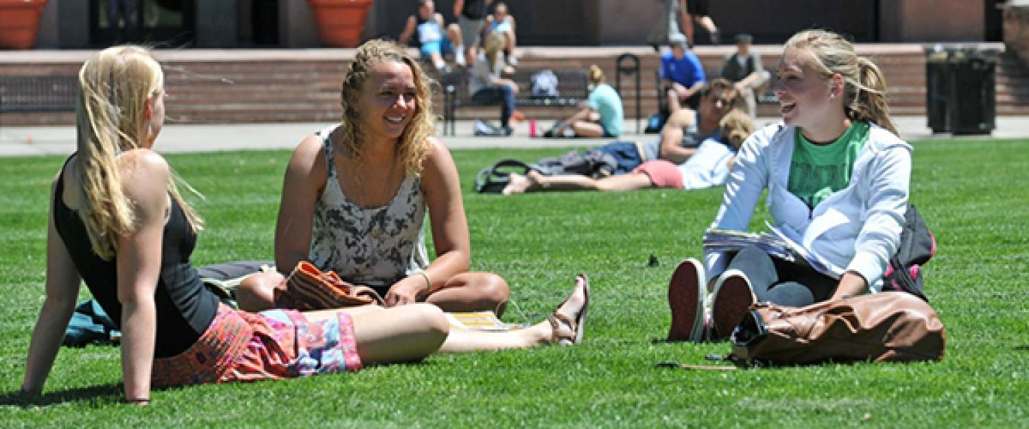 Students sitting in the grass on the quad at CU Boulder