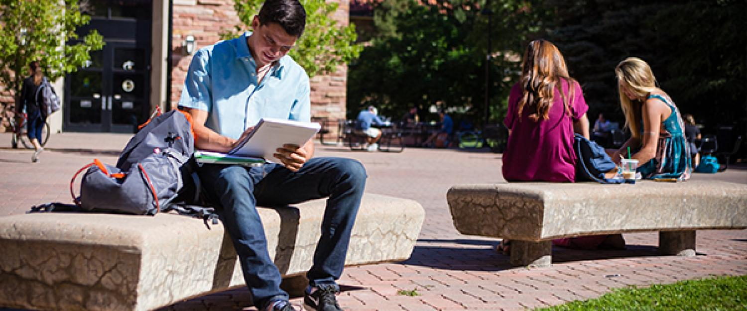 A high school student studies on a bench in the sunshine outside the UMC.
