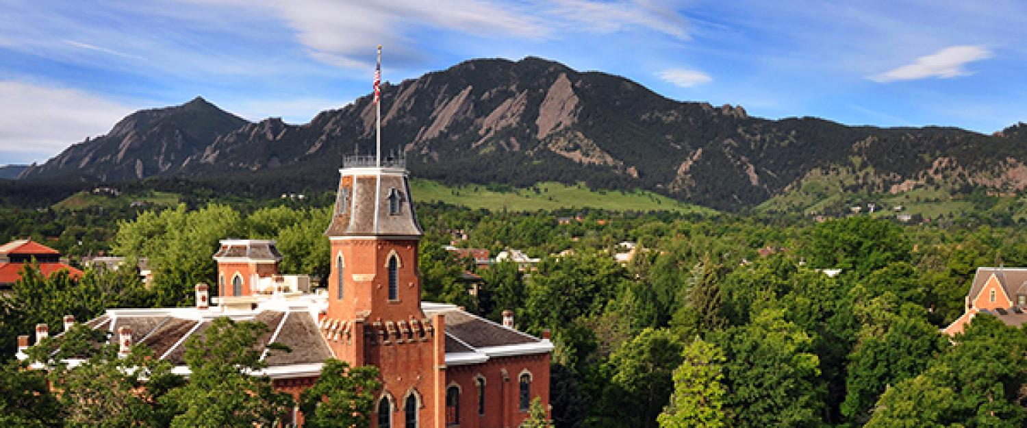 Arial view of the CU Boulder campus including Old Main and the Flatiron mountains in the background.