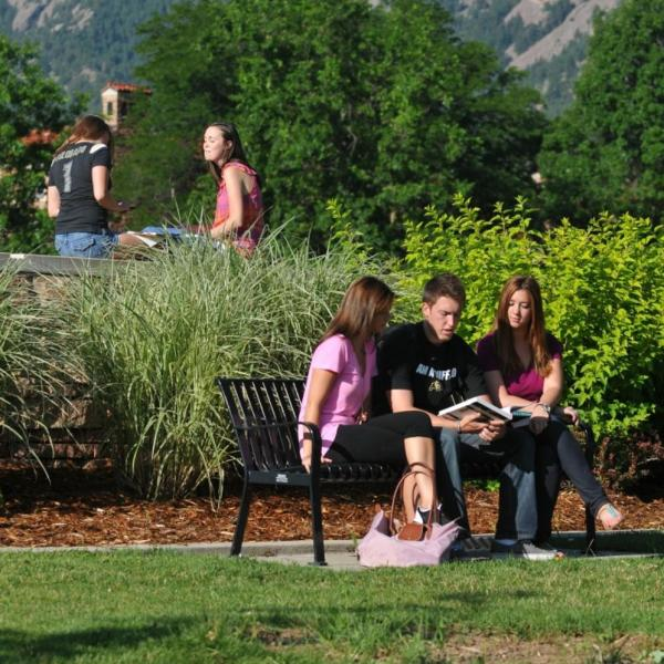 students sitting outside with the mountains in the background