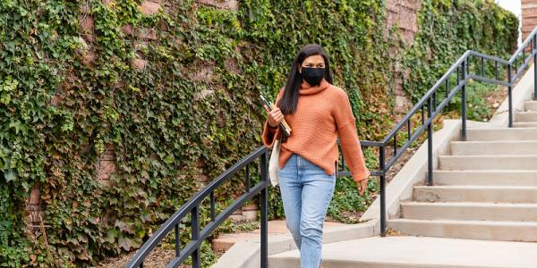 Student walking on campus with books in hand, wearing a face mask.