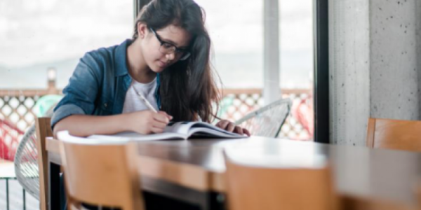 Student sitting at table with book.