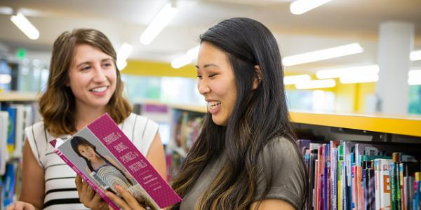 Two Education students browse children's books in a colorful library.