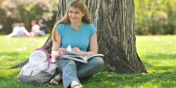 Student reads a textbook outside