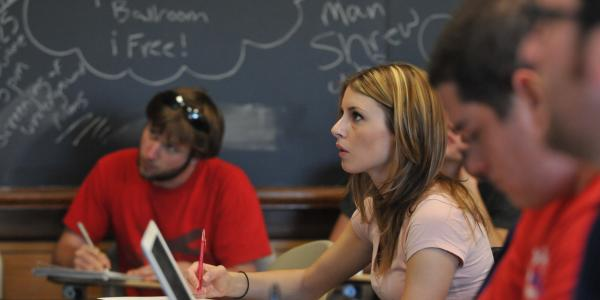 Student looks at instructor in small classroom