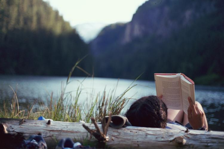 Girl reading a book by the water.