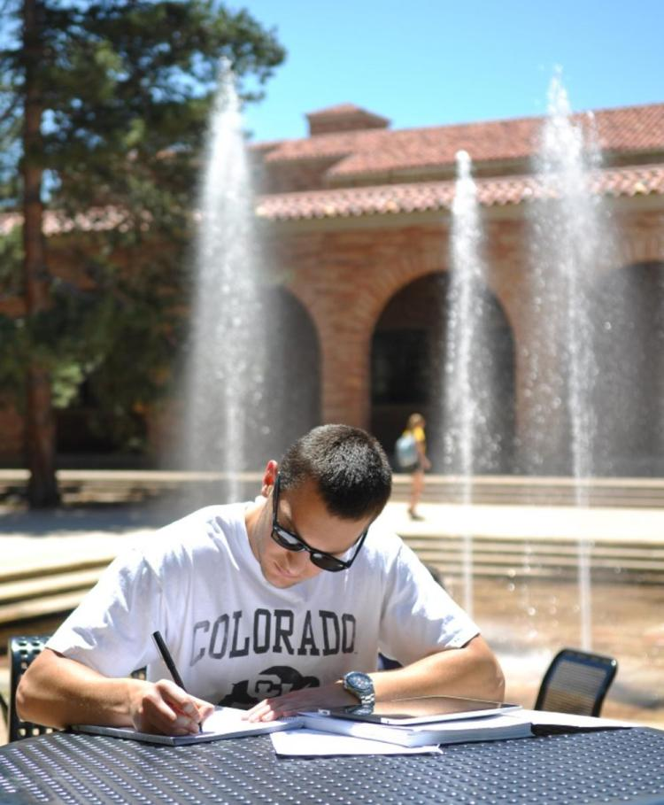 male student working outside at a table
