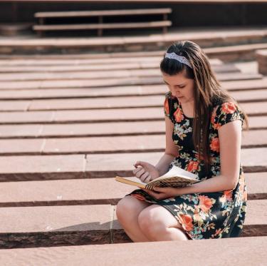 Female student studies outside.