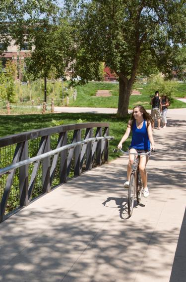 A student riding a bike on a bridge.